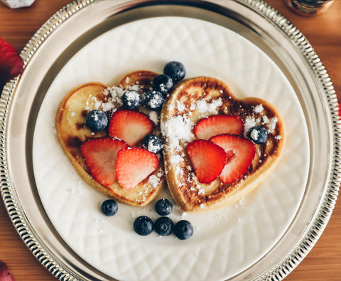 heart-shaped pancakes covered with strawberries blueberries and sugar powder