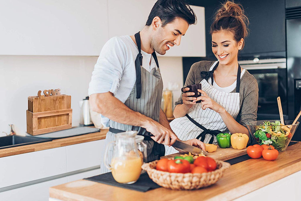 happy couple in the kitchen cooking with bamboo cutting board set