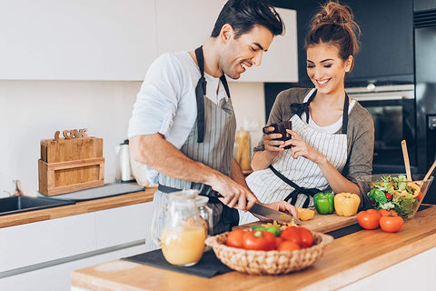 Image of happy couple in the kitchen cooking with bamboo cutting board set