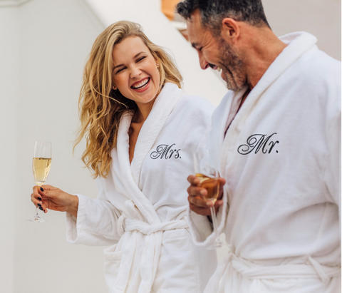 Image of happy couple enjoying champagne dressed in matching mr and mrs robes