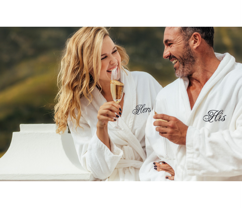 happy couple enjoying champagne dressed in matching his and hers robes