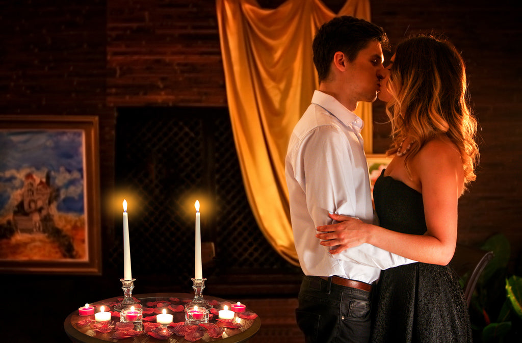 couple kissing surrounded by romantic night decorations