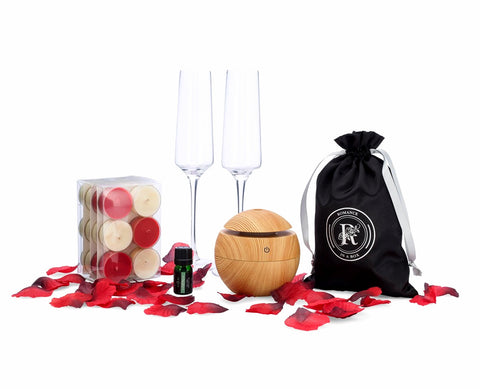 Image of tea light candles flutes rose petals essential oil diffuser and essential oil