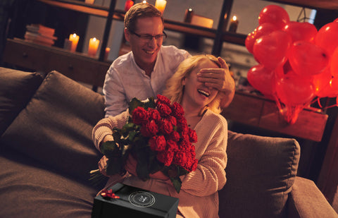 Image of man surprising a woman with romantic gift and flowers on their anniversary