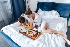 couple embracing and enjoying a beautiful breakfast in bed