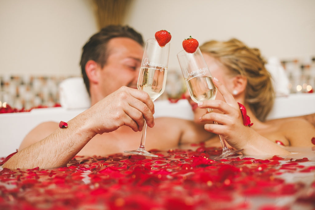 happy couple taking a romantic bath with rose petals and drinking champagne