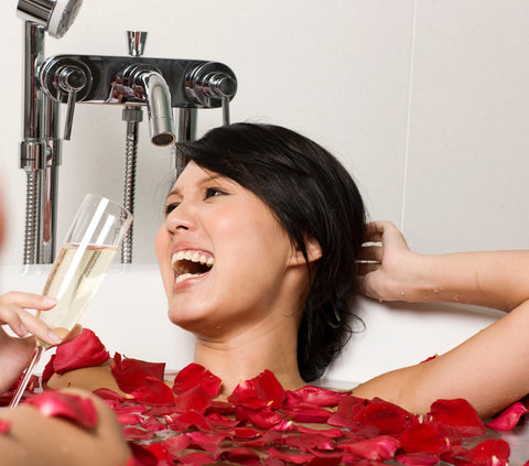 Image of happy woman in a bathtub with rose petals drinking champagne