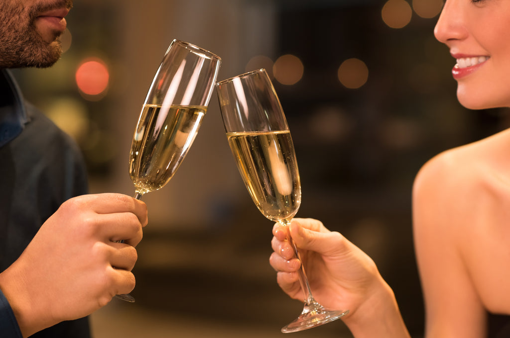 couple clinking champagne to celebrate their anniversary with romantic dinner