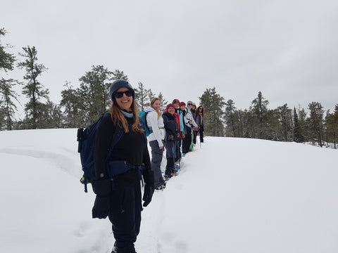 a group of Backcountry Women lined up in the snow with snowshoes, smiling