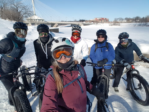 women with their faces covered by goggles and balaclavas, wearing bike helmets while posing with their fat tire bikes in front of the iconic Esplanade Riel bridge in Winnipeg