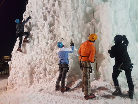 four women starting to climb a lit up ice tower at night in Winnipeg