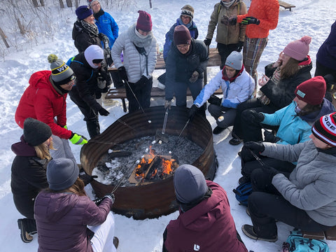 a large group of Backcountry Women gathered around a large fire pit - they are leaning toward the fire with their marshmallows on roasting sticks