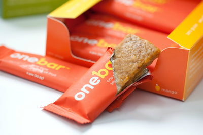 Onebar mango flavor partially opened in front of box of 12 bars.