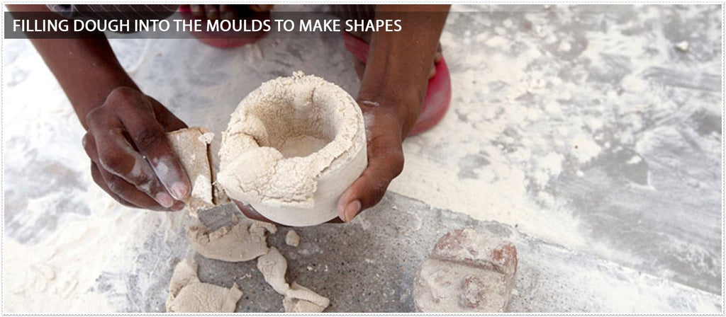 filling dough into the moulds to make shapes