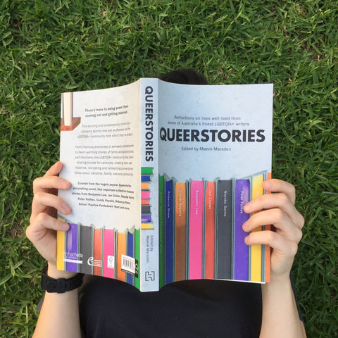 Image shows a photo taken from above; a person lays on green grass reading a book called 'Queerstories' which obscures their face
