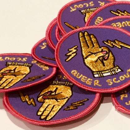 Image shows a scattered pile of iron-on patches. The patches are purple with a pink edge and say Queer Scout in gold with a gold hand and lightening bolts