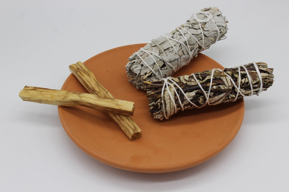 "4"" WHITE SAGE YERBA SANTA SMUDGE STICKS PALO SANTO WOOD ON TERRACOTTA PLATE GIFT SET. This gift set comes with two white sage yerba santa smudge sticks and two palo santo wood on an orange terracotta plate."