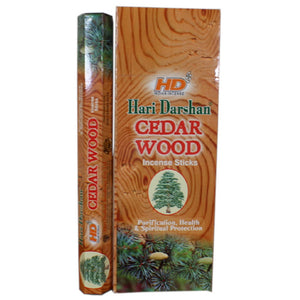hari darshan cedar wood box with single packet standing next to it with cedar branch at the bottom of the box design and a wood background