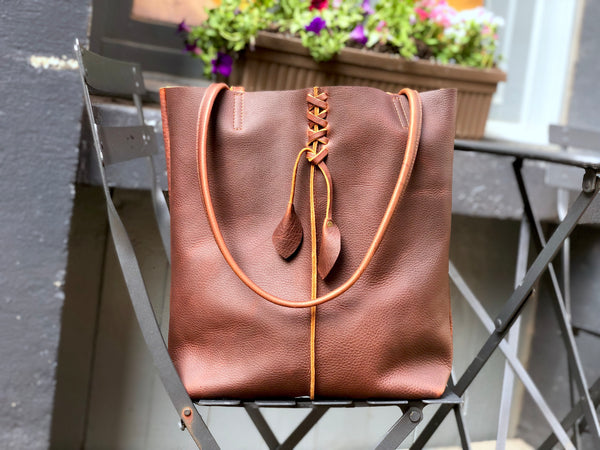 Tall brown leather tote with middle stitch and leaf tassels