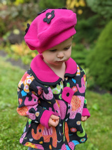 Young girl wearing a handmade elephant-patterned coat and a homemade pink flower hat