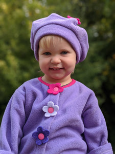 Young child wearing a purple children's coat with flowers and matching children's hat