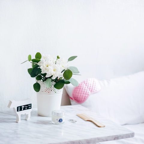 A plant inside a white plant pot sits on a bedside table. A pink sleep mask is visible sits on a pillow in the background.