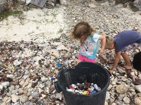 Kids collecting plastic off the beach and putting it in a bin