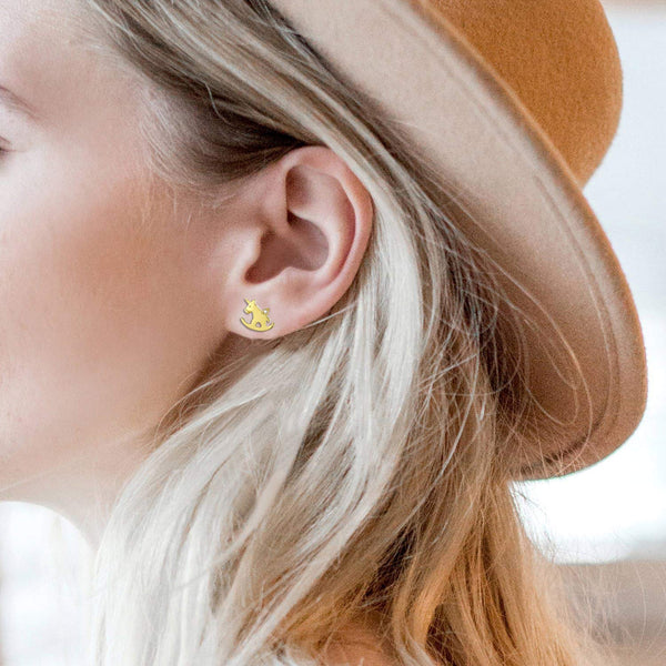 Female Model Wearing Unicorn Earrings in Gold Colour