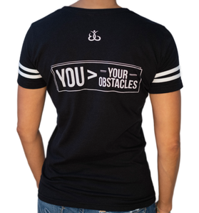 Your Obstacles Tees For Women | Back view of women's black varsity tee with two white stripes on sleeves and BackGetters in white across the chest