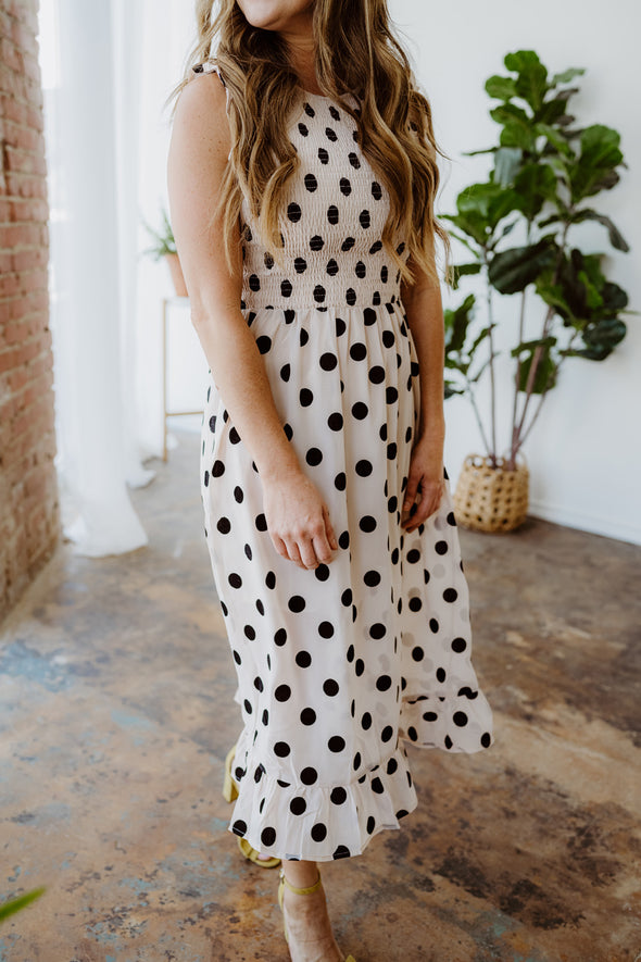 Jamie wears the Spotted in Style Dress, a midi length blush dress with black velvet polka dots, smocked bodice, and ruffle sleeves.
