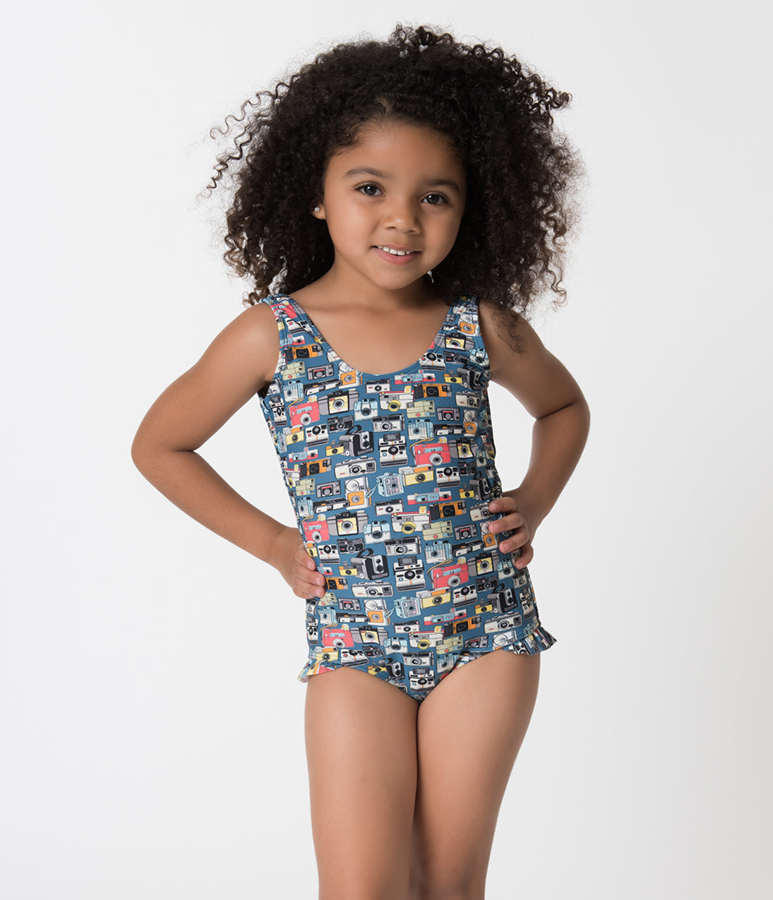 Retro Style Blue Vintage Camera Tank Style Kids One Piece Swimsuit With little cameras to capture the big picture, this one piece tank is perfect for your little superstar! The retro inspired swimwear is printed with a multicolored vintage camera design, keeping the past alive with just a snapshot. Small ruffles sit on the top of the low cut legs of this fully lined swimmer. Created from a stretch friendly fabric blend, your little one will be ready for her close up! ..Available in sizes 2-6 while supplies last. | Retro Style Blue Vintage Camera Tank Style Kids One Piece Swimsuit