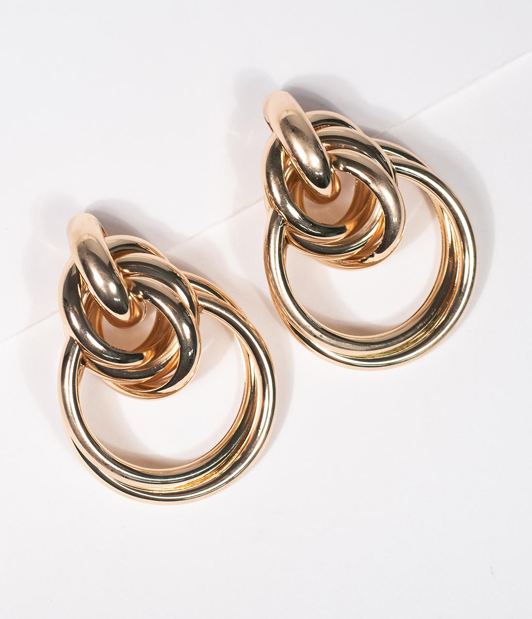 Gold Knot Drop Earrings When in doubt, add a little flash of gold! Two golden knotted hoop earrings are a striking metallic accessory to your vintage ensemble. Secured by post backing, perfect for a fashion icon!.Available while supplies last. | Gold Knot Drop Earrings