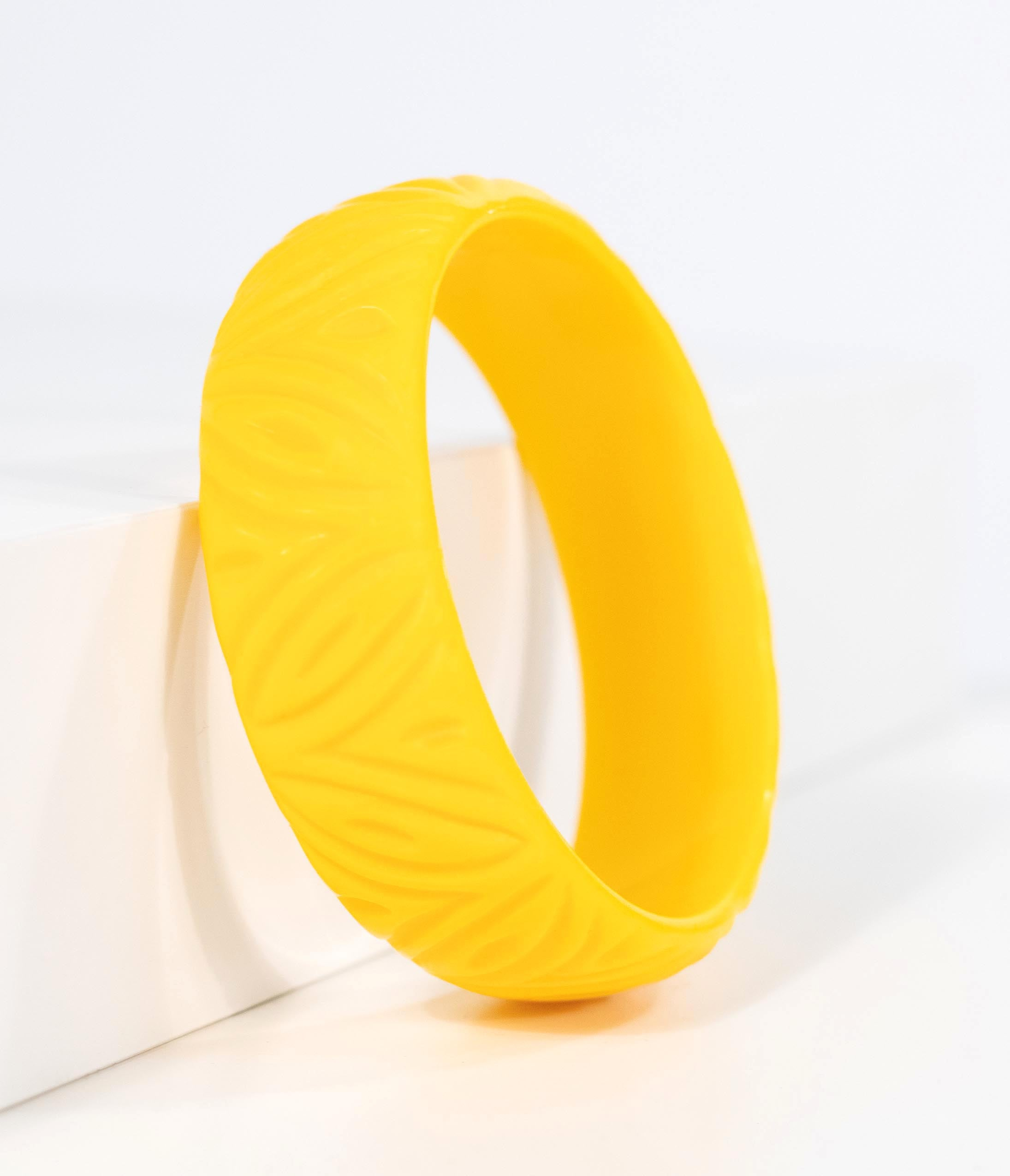 1950s Jewelry Styles and History Banana Yellow Carved Resin Bangle Bracelet $17.00 AT vintagedancer.com