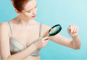 Girl checking for skin cancer with magnifying glass