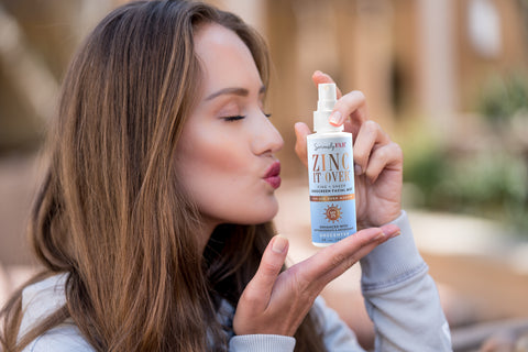 Beautiful model with long hair kissing bottle of over makeup sunscreen mist