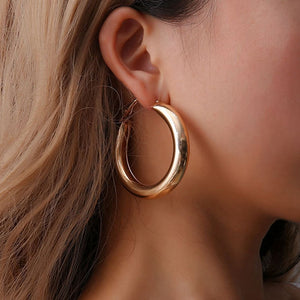 "Stay on trend this season with these Thick Hoop Earrings featuring a solid color and a thick round hoop. Choose from gold tone or silver plated. Delivery 4-13 days. From our unique boutique. Description: Type: Hoop, Color: Solid, Metal: Alloy, Size: 2.2"" (H) x 0.4"" (W), Diameter: 2""."