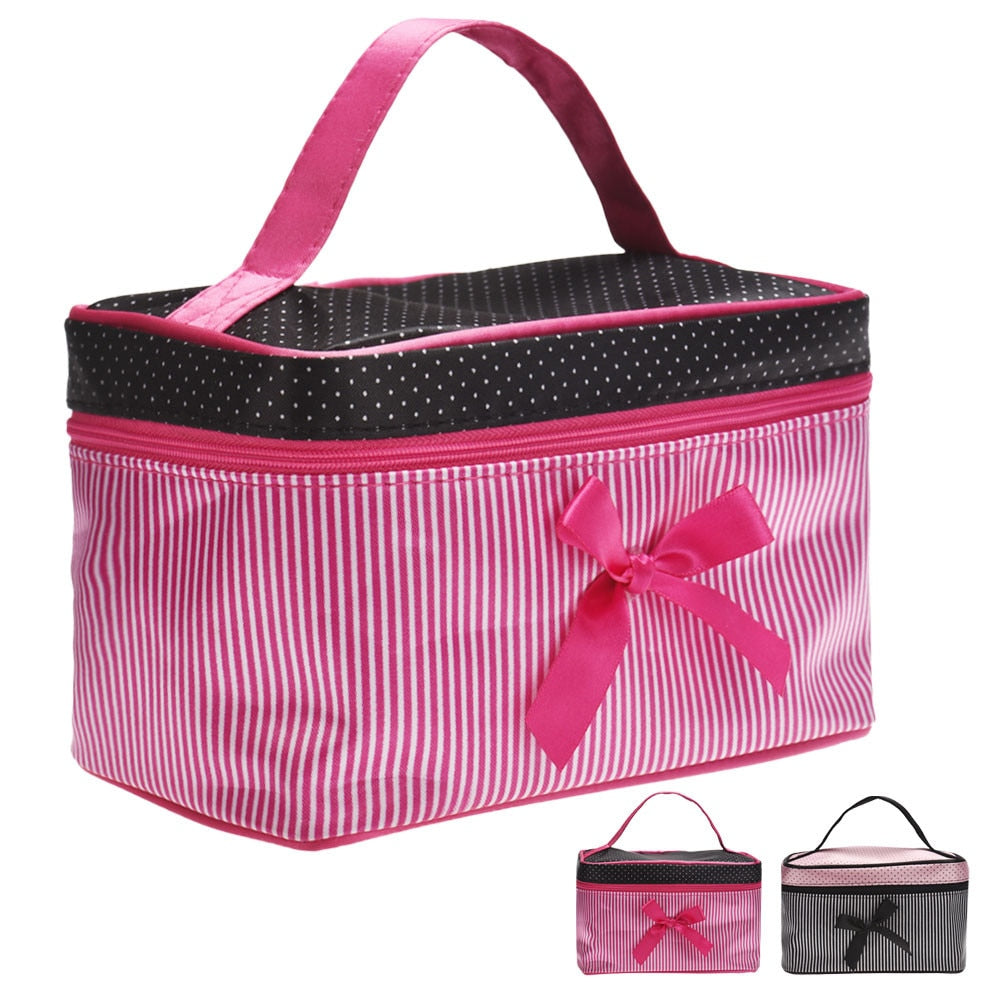"This handy Cosmetic Bag is sure to hold all your essentials. Featuring a single handle, striped and polka dot pattern, a front bow and double zipper closure. Choose from 2 colors. From our Utterly Unique Boutique. Description: Number Of Handles: Single, Material: Satin, Hardness: Soft, Fashion Element: Bow, Closure: Double Zipper, Pattern: Striped, Polka Dot, Size: 7.5"" x 4.5"" x 4""."