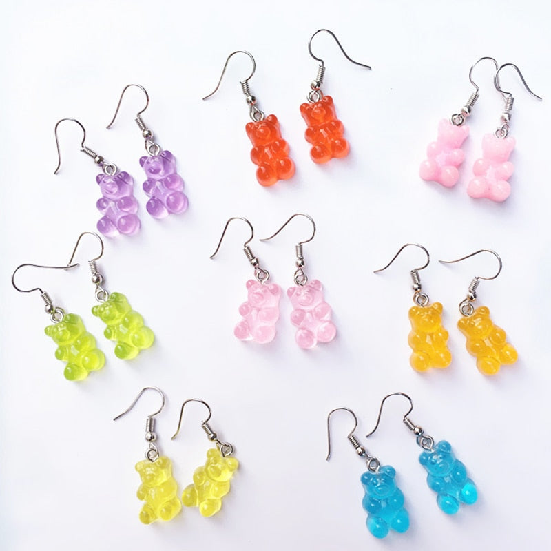 "Wearing these cute Gummy Bear Earrings shows your love for gummy bears and will compliment any outfit in your wardrobe. They feature a hook closure. Choose from 8 fun summer colors. Delivery 4-13 days. From our Utterly Unique Boutique. Description: Closure: Hook, Metal: Alloy, Material: Resin, Shape: Bear, Size: 0.4""."