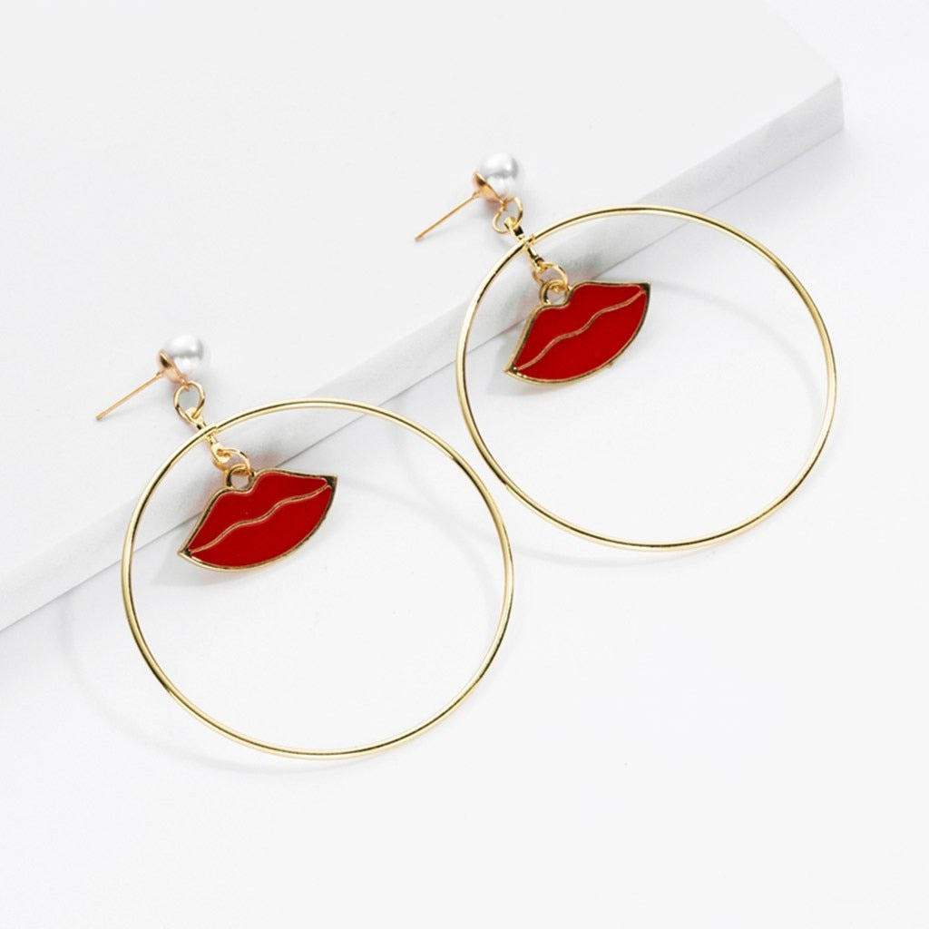"Mix it up with these super cute Lip Earrings. Featuring a gold-tone with lips in the middle of a circle and a simulated pearl. Choice of color red. From our Utterly Unique Boutique. Description: Type: Drop Earrings, Pattern: Lip, Metal: Alloy, Backing: Post, Length: 3"" (H) x 2"" (W)."