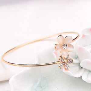 "Trendy and versatile, this Double Floral Bracelet slips on your wrist, has 2 flowers with rhinestones and looks great. Easily pair with anything in your wardrobe. Color gold plated. Delivery 5-9 days. From our Utterly Unique Boutique. Description: Material: Metal, Closure: Open, Shape: Flowers Metal: Alloy, Diameter: 3"", Fashion Element: Rhinestones."