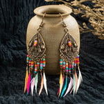 "Make a statement with these Long Beaded Feather Earrings. They feature a hook backing, multi-colored rows of beads and 7 multi-colored feathers. Choose from gold tone or silver. Delivery 4-13 days. From our unique boutique. Description: Type: Drop Earrings, Metal: Alloy, Material: Feathers, Beads, Closure: Hook, Size: 3.9"" x 0.8""."