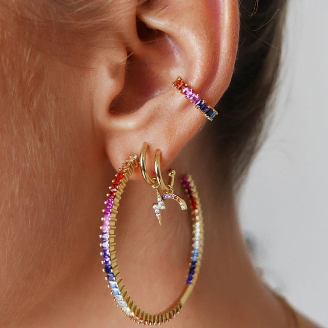 "Make a statement with this Four Piece Earring Set. This matching set features crystals, a hoop earring, 2 smaller hoops with dangling charms and a small ear cuff. Color multi-colored. Delivery 4-13 days. Limited stock. From our unique boutique. Description: Shape: Round, Metal: Alloy, Material: Crystal, Closure: Push Backing, Includes: 4 Pieces, Fashion Element: Charms, Large Hoop Size: 1.6"" long x 1.7"" wide, Charm Sizes: 0.5"" long x 0.1"" wide And 0.3"" long x 0.4"" wide, Cuff Size: 0.5"" long x 0.5"" wide"