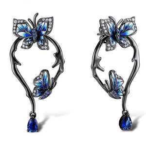 "Jump into spring with these fun Blue Butterfly Earrings! Featuring two blue butterflies surrounded by crystals on a stem and a push-back closure. Color blue. Delivery 4-13 days. From our Utterly Unique Boutique. Description: Material: Metal, Crystals, Pattern: Butterflies, Stem, Backing: Push Back, Size: 1."" x 0.8""."