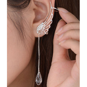 "Angel Wing Earrings - Utterly Unique Boutique - $4.99 - Ships FREE - Put on a pair of these angel wings and make a statement. These earrings are bold and will stay in place with a post backing and an ear wrap. They feature an angel wing pattern, a chain and crystal. Available in silver. From our Utterly Unique Boutique. Description: Metal: Zinc Alloy, Material: Metal, Shape: Angel Wings, Fashion Element: Crystal, Wing Size: 1.6"" x 0.6"