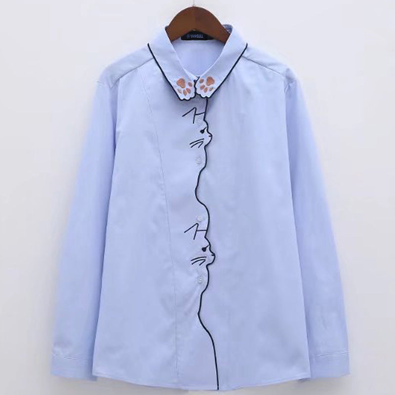 Embroidered Cat Blouse - Utterly Unique Boutique - Very Cool Embroidery! - This blouse is part of a collection from our unique boutique and features an embroidered cat down the front with a paw print on the collar, long sleeves and a turn-down collar with a button up front. Your choice of blue or white.