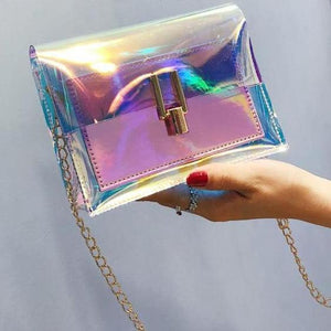 Iridescent Crossbody Bag - Utterly Unique Boutique - NEW - FREE Ship - This beautiful little crossbody bag will show luminous colors that seem to change when seen from different angles. It has enough room to fit your essentials, comes with a single chain strap and has a flap with a clasp closure. Choose from 3 fun colors. From our Utterly Unique Boutique. Description: Material: PU, Number of