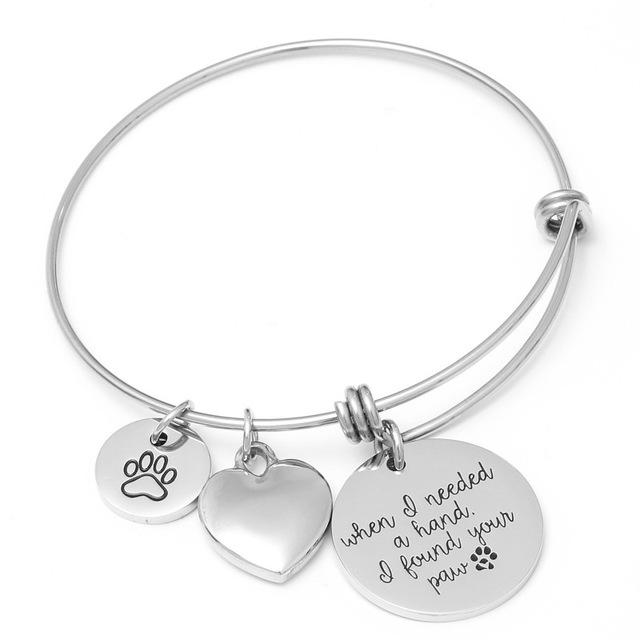 "Versatile and powerful, this Paw Bracelet has a message to deliver! It features three charms, is adjustable and is made from stainless steel so it won't rust, stain or corrode. Also available without the message. Easily pair with anything in your wardrobe. Color silver. From our Utterly Unique Boutique. Description: Bracelet Size: .063"" x 2.5"" Adjustable, Fashion Element: Three Charms, Metal: Stainless Steel."