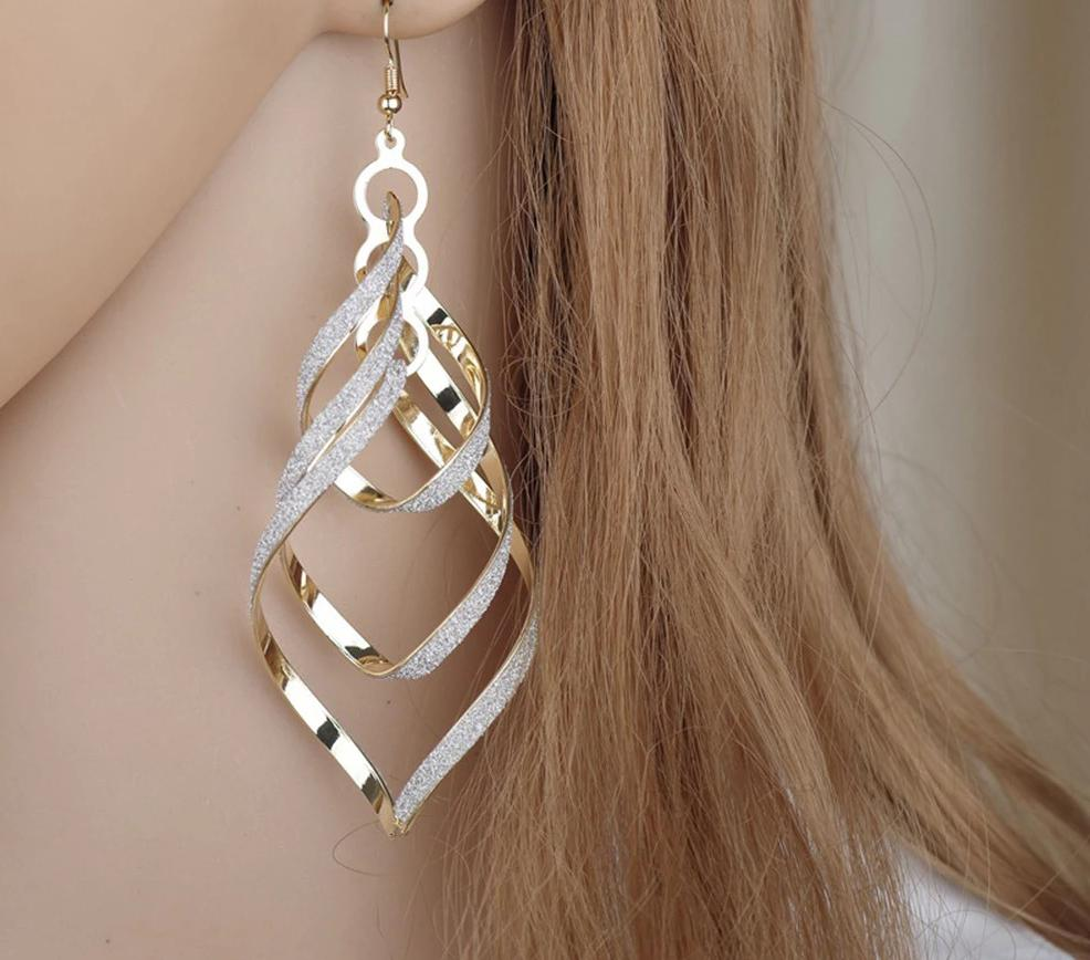"These pretty Spiral Drop Earrings are spot on for an evening out. They're unique, light and feature a long spiral shape that shines, have a hook closure and are sure to be an eye catcher. Choose from black, gold or silver. From our be unique boutique. Description:Material: Aluminium Alloy, Shape: Spiral, Closure: Hook, Size: 4.3"" high x 1.4"" wide."