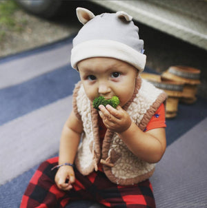 Baby eating while wearing mouse baby hat