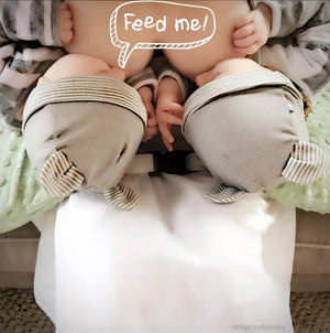 Breastfeeding twins wearing baby hats